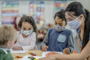 Group of children coloring while wearing masks - best school supply list for k-12 students