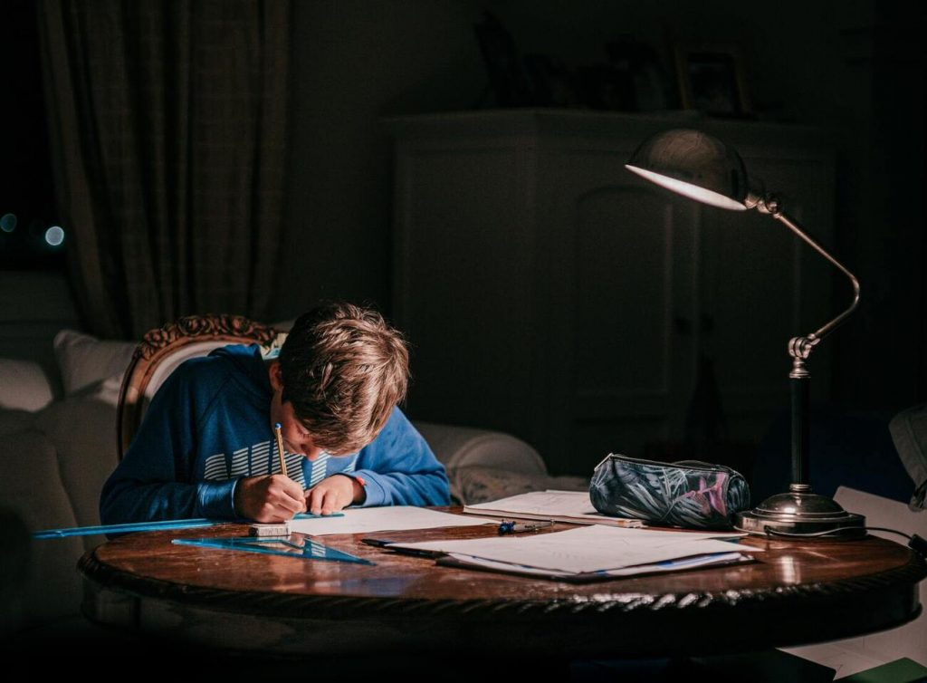 A boy in a dark room studying for an exam
